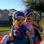 Girls ready to go to the playground, wearing hats from Nana.